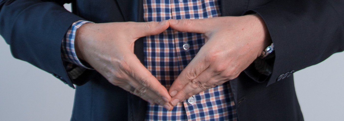 Der Bildausschnitt zeigt Mann im blauen Jacket und karietem Hemd, welche auf Höhe von Bauch gezeigt wird. Die Hände formen die typische Merkel-Raute.