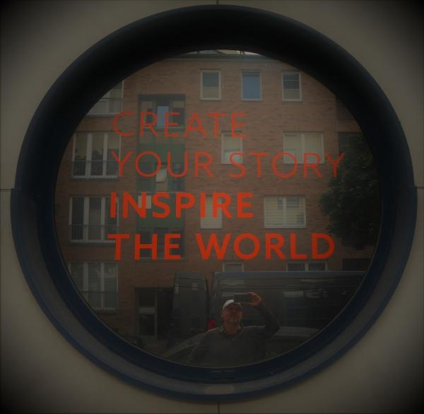 """Bild zeigt ein Fenster in Bullaugen-Form, auf der man in roter Schrift lesen kann: """"Create your Story, Inspire the World"""". In der Spiegelung der Fensterscheibe ist der Autor Ralph Raule schemenhaft zu erkennen, wie wer das Bild fotgrafiert."""